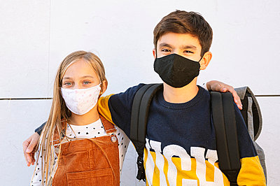 Brother and sister wearing protective face mask standing against wall on sunny day - p300m2225898 by Jose Luis CARRASCOSA