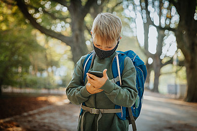 Boy text messaging on smart phone wearing protective face mask while standing in public park - p300m2226881 by Mareen Fischinger