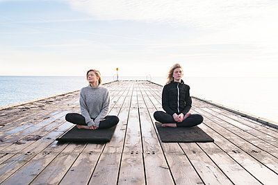 Two women meditating on pier - p312m1471989 by Viktor Holm