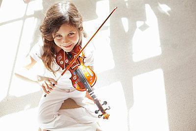 Girl playing violin on carpet - p42916570f by Axel Bernstorff