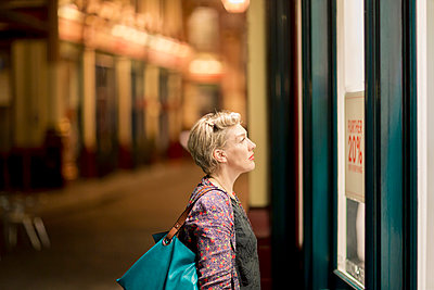 Mature woman looking at shop window at night, London, UK - p429m999612 by dotdotred