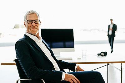 Mature businessman at desk - p586m1208545 by Kniel Synnatzschke