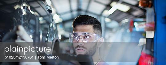 Focused male mechanic examining car in auto repair shop - p1023m2196761 by Tom Merton