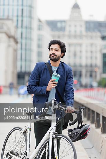 Smiling businessman with coffee and bicycle on city bridge - p1023m2208411 by Paul Bradbury