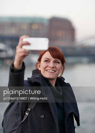 Frau macht Selfie - p1124m1216807 von Willing-Holtz