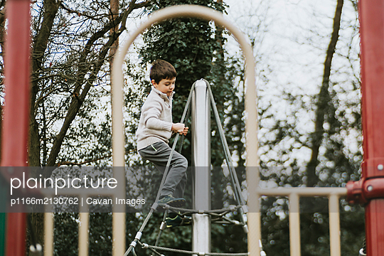 Side view of child at top of climbing frame at playground - p1166m2130762 by Cavan Images