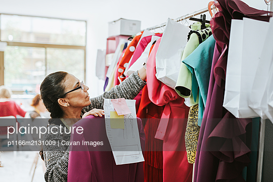 seamstress placing clothes in the design studio - p1166m2131009 by Cavan Images