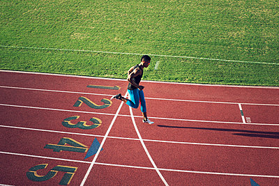 High angle view of male athlete crossing finish line on field - p1166m1088140f by John Trice