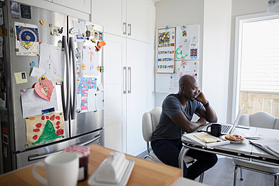 Mature African American man talking on cell phone and working at laptop at kitchen table - p1192m1490807 by Hero Images