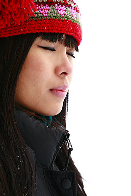 Asian girl outside in winter with eyes closed. - p1328m2081813 by Pierre Desrosiers
