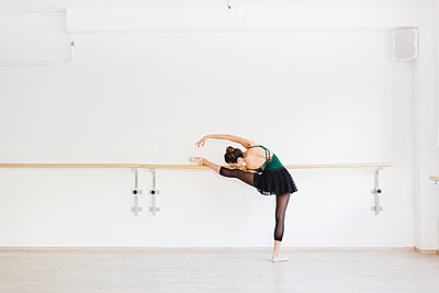 Dancer practicing at the barre in the gym - p300m1113314f by Michela Ravasio