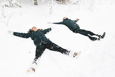 Finland, Jyvaskyla, Saakoski, Young couple making snow angel - p352m1141632 by Eija Huhtikorpi