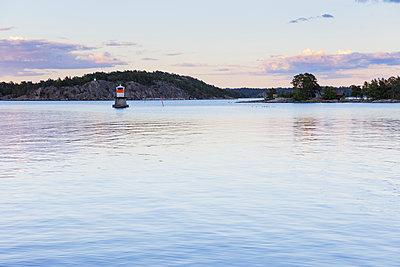 Sweden, Sodermanland, Dalaro, Korsholmen, Seashore with lighthouse at sunset - p352m1349342 by Gustaf Emanuelsson