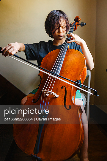 Close-up of a boy with intense focus playing cello in a stairwell - p1166m2268854 by Cavan Images