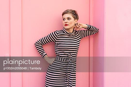 Blonde Frau in gestreiftem Kleid steht vor einem pinkem Haus - p1332m2055048 von Tamboly