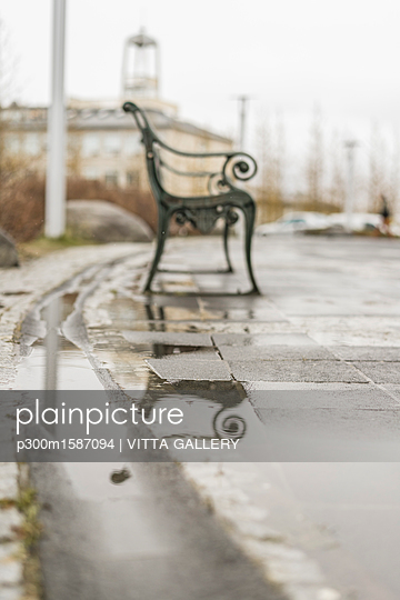 Empty bench feflecting in puddle on a rainy day - p300m1587094 von VITTA GALLERY