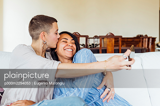 Young woman embracing and kissing girlfriend while taking selfie through smart phone at home - p300m2294053 by Eugenio Marongiu