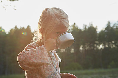 Girl drinking from camping cup - p1023m1172702 by Francis Pictures