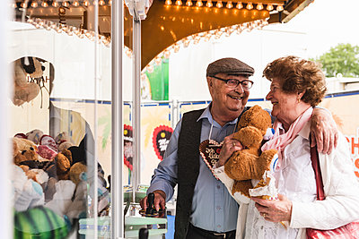 Happy senior couple with prize on fair - p300m1587300 by Uwe Umstätter
