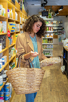 Young woman shopping in a food shop - p300m2118561 by VITTA GALLERY