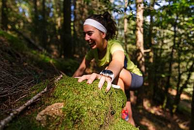 Active female athlete climbing rock in forest - p300m2282418 by Mikel Taboada