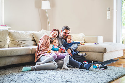 Portrait of happy parents sitting with children in living room at home - p426m2127363 by Maskot