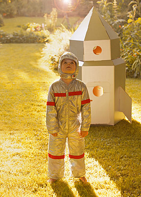 Boy Wearing Space Suit Standing in front of Cardboard Rocket Spacecraft - p669m713956 by Jutta Klee photography