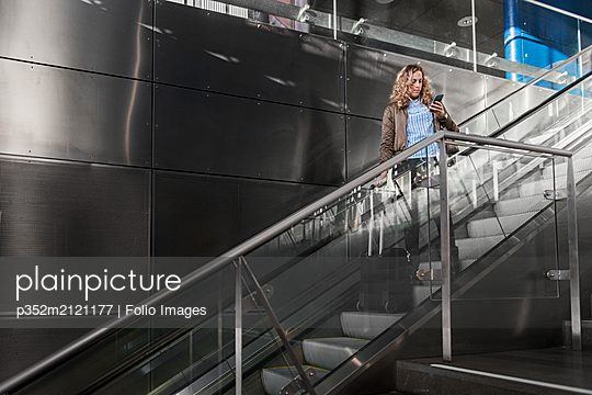 Young woman looking at cell phone on staircase - p352m2121177 by Folio Images