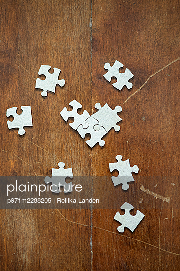 Puzzle pieces on wooden table - p971m2288205 by Reilika Landen