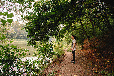 Side view of woman looking at lake while standing at lakeshore - p1166m2095798 by Cavan Images