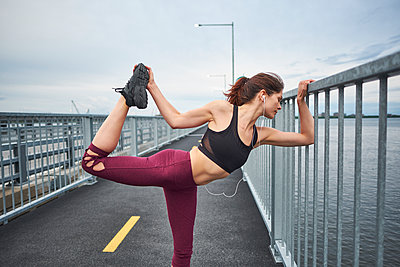 Confident woman warming up for training on bridge, Montreal, Quebec, Canada - p1362m1530070 by Charles Knox
