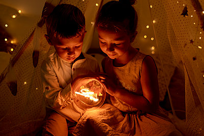 Sibling holding light while sitting in room during christmas - p300m2220932 by Gala Martínez López