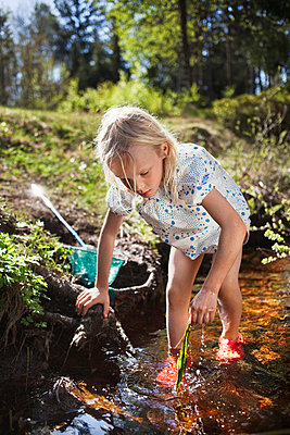 Girl playing in creek - p42916132f by Christoffer Askman