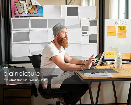 Designer sitzt am Schreibtisch - p1124m1162052 von Willing-Holtz