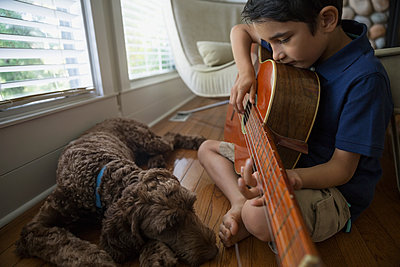 Dog sleeping next to boy playing guitar - p1192m1078240f by Hero Images