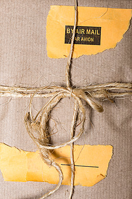 Artistically wrapped parcel in brown paper with yellow airmail shipping labels. - p1433m1586546 by Wolf Kettler
