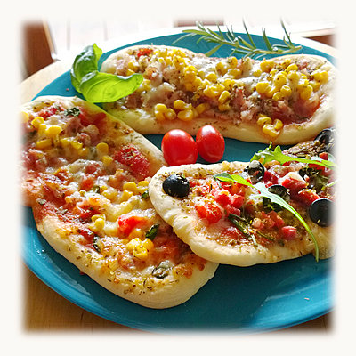 Pizza rolls, topped with tomato, mozzarella, arugula, corn, salami, ham, olives, Studio - p300m1008795f by Roman Märzinger