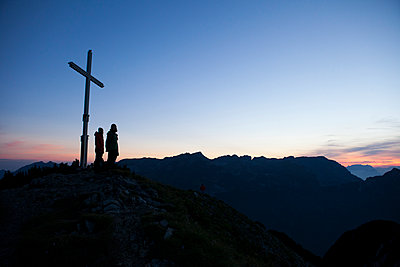 Austria, Tyrol, two hikers standing at summit cross - p300m1549519 by Anita Fuchs
