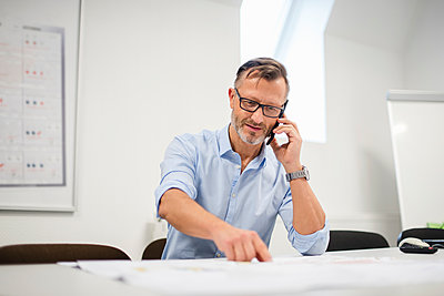 Mature businessman talking on phone at desk in office - p300m1562932 by Daniel Ingold