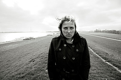 Young woman on a dyke, Hamburg, Germany - p341m1025618 by Mikesch