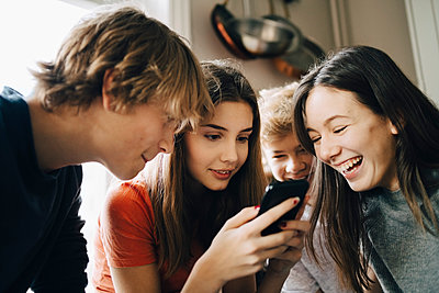 Close-up of cheerful friends looking at mobile phone in kitchen - p426m1555872 by Maskot