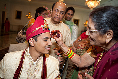 Indian woman marking groom's face - p555m1479677 by Jihan Abdalla