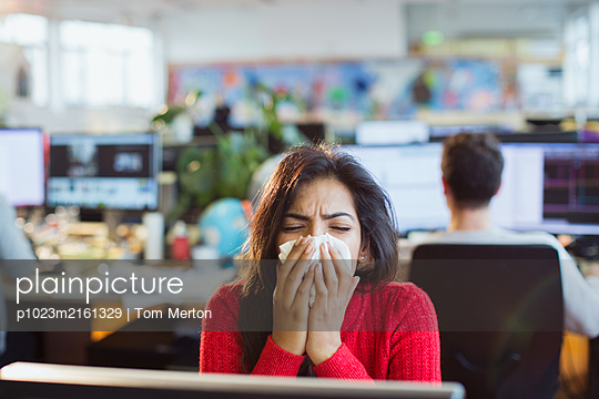 Businesswoman with allergies sneezing into tissue at computer in office - p1023m2161329 by Tom Merton