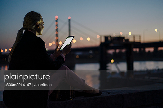 Female professional using digital tablet while sitting on retaining wall at dusk - p300m2214147 by Joseffson