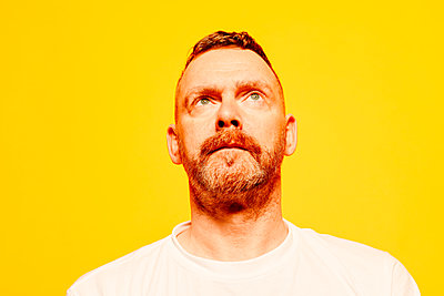 Red-haired man in front of yellow background, portrait - p1267m2272511 by Jörg Meier