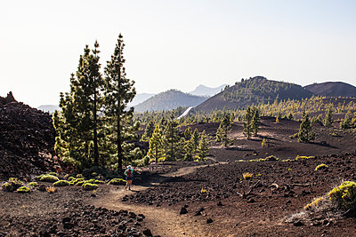 Hiker in lava bed - p1291m1465794 by Marcus Bastel