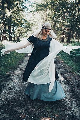 Blonde Frau im Märchenkostüm tanzt auf einem Waldweg - p1628m2211444 von Lorraine Fitch