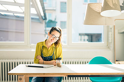 Smiling freelancer sitting at desk in her studio - p300m1581046 von Robijn Page