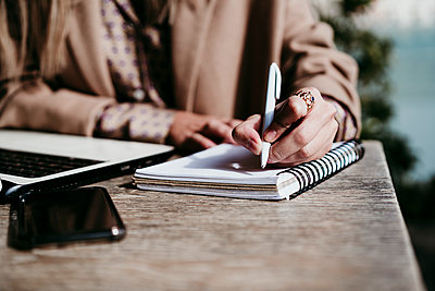 Businesswoman writing on diary at desk in office - p300m2240236 by Eva Blanco