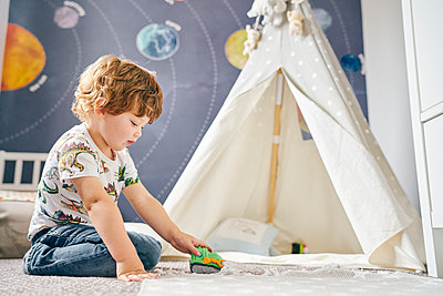 Toddler playing in room, child's teepee, mural of solar system on wall - p429m2164638 by GS Visuals